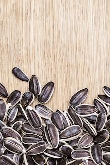 Graines de tournesol de haute qualité sur fond en bois avec espace de copie. graines non pelées. format vertical.