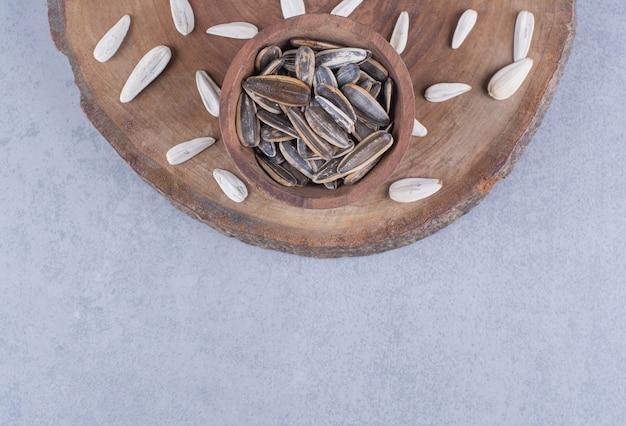 Graines de tournesol noir et blanc dans des bols sur une planche sur la surface en marbre