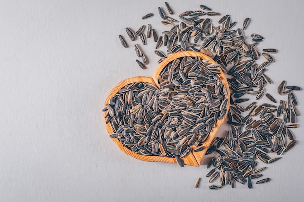 Graines de tournesol noir sur planche en forme de coeur et fond blanc, vue de dessus.