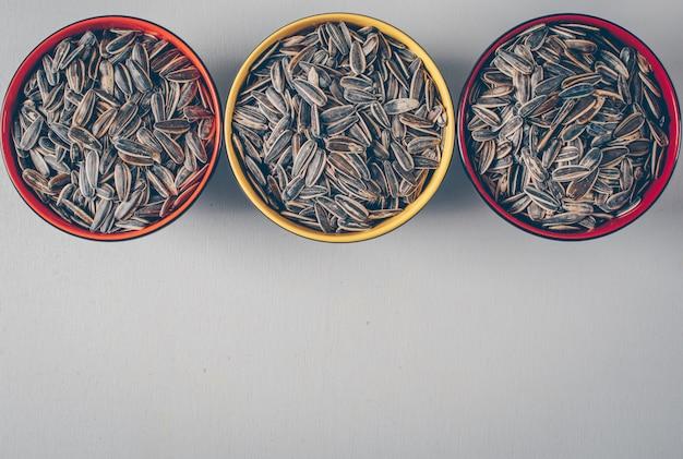 Graines de tournesol noires dans des bols sur fond blanc. vue de dessus. espace pour le texte