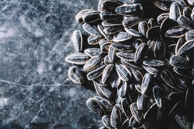 Graines de tournesol noires sur fond de marbre