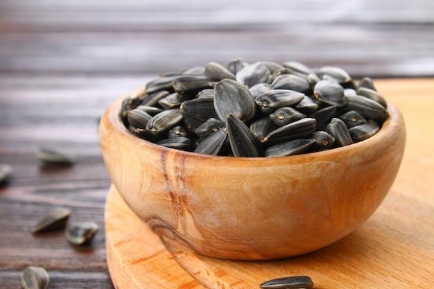 Graines de tournesol noires non raffinées dans un bol en bois sur une table en bois.