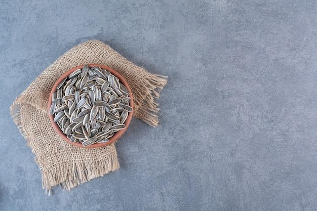 Graines de tournesol non pelées dans une plaque d'argile sur la texture, sur la surface en marbre
