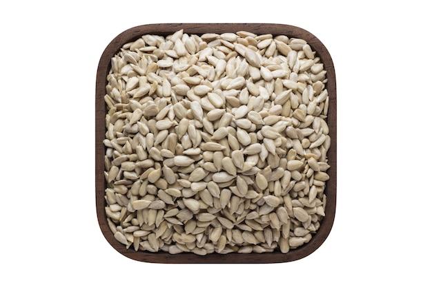 Graines de tournesol pelées dans un bol carré isolé sur fond blanc. aliments biologiques, vue de dessus.