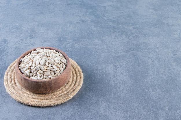 Graines de tournesol pelées dans un bol sur le dessous de plat sur la surface en marbre