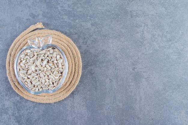 Graines de tournesol pelées dans un bol en verre sur le dessous de plat sur la surface en marbre