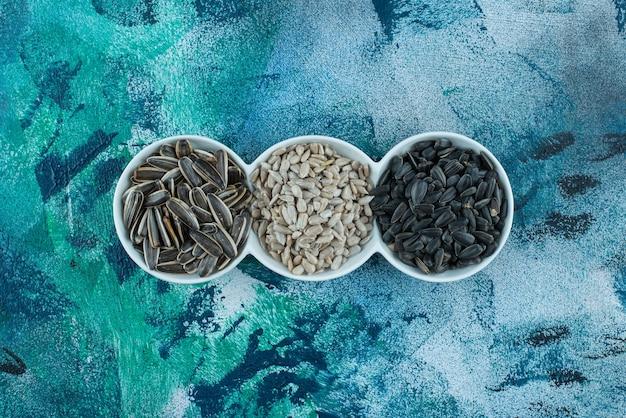 Graines de tournesol pelées et non pelées dans un plateau sur la surface en marbre