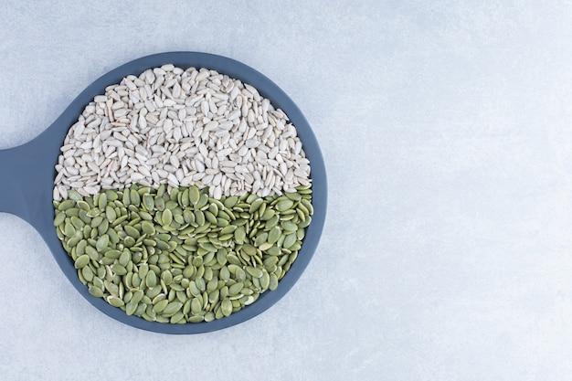 Graines de tournesol et pepitas assorties sur un petit plat de service sur fond de marbre.