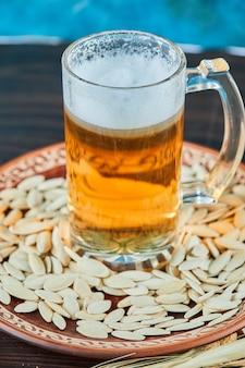 Graines de tournesol et un verre de bière sur une table sombre.