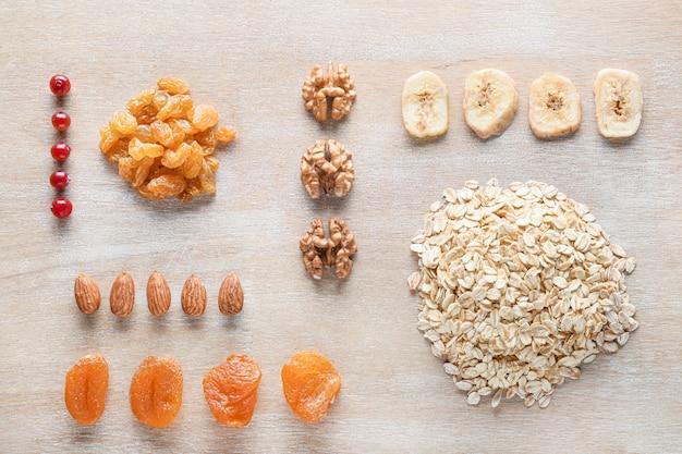 Grains d'avoine secs avec fruits et noix sur bois