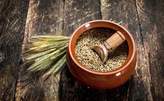 Grains de blé dans un bol. sur un fond en bois.
