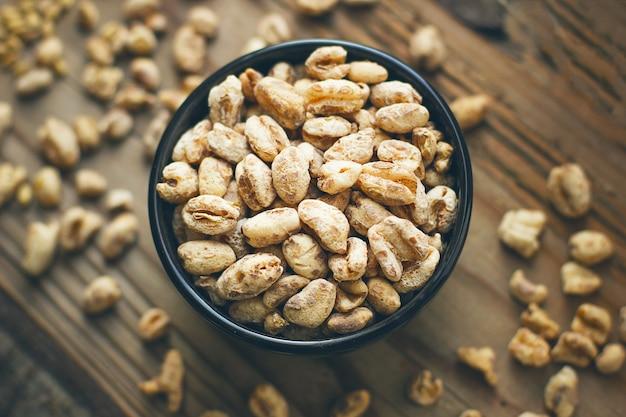 Grains de blé dans un bol et maïs soufflé dans un bol, semences de blé rustique