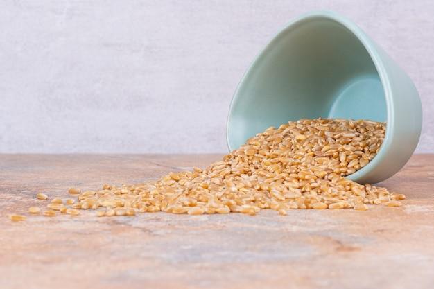 Grains de blé secs dans un bol renversé, sur le marbre.