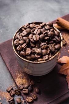 Grains de café à angle élevé en tasse sur une planche à découper avec de la cannelle