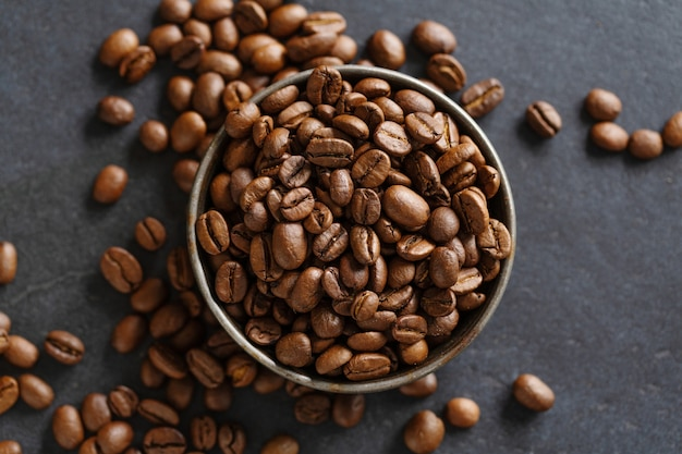 Grains de café arabica dans un bol sur fond gris. vue d'en-haut.