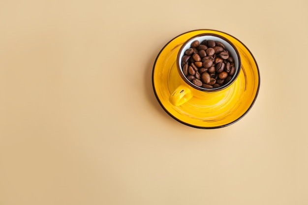 Grains de café arabica dans une tasse jaune design avec soucoupe papier beige pastel
