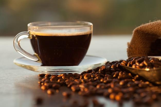 Grains de café arabica torréfié noir et tasse pleine de café