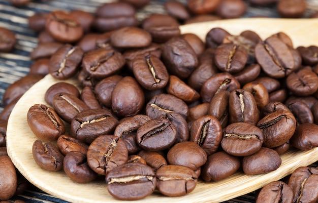 Grains de café aromatiques dans une cuillère en bois