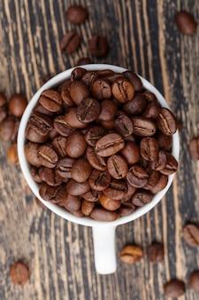 Grains de café aromatiques dans une tasse, grains de café pour préparer un délicieux café dans une tasse