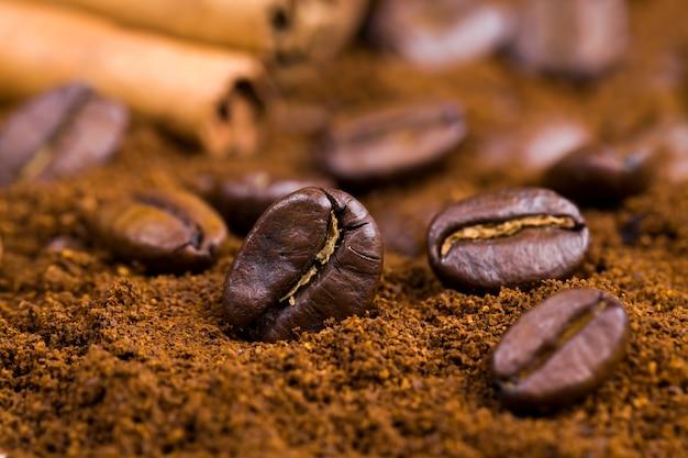 Grains de café aromatiques pendant la préparation de la boisson, grains de café entiers délicieux et parfumés à la surface, gros plan