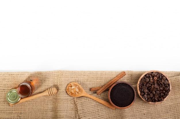 Grains de café au miel sur toile de jute isolé sur fond blanc