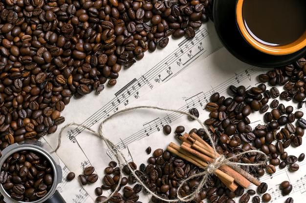 Grains de café, bâtons de cannelle et tasse de café infusé sur fond de partition, vue d'en haut avec un espace pour le texte. nature morte. maquette. mise à plat