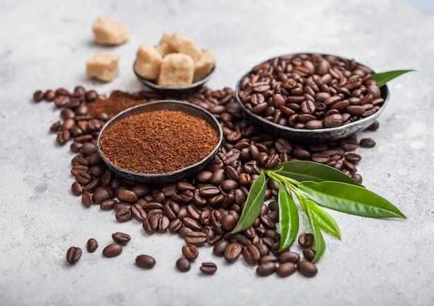 Grains de café biologiques bruts frais avec poudre en poudre et cubes de sucre de canne avec une feuille de café sur une table de cuisine claire.