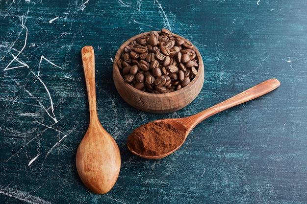 Grains de café brun dans une tasse et des cuillères en bois.