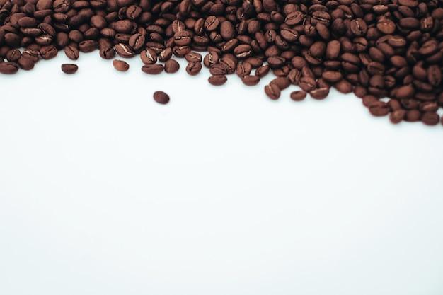 Grains de café brun foncé aromatiques isolés sur fond blanc vue de dessus avec espace de copie