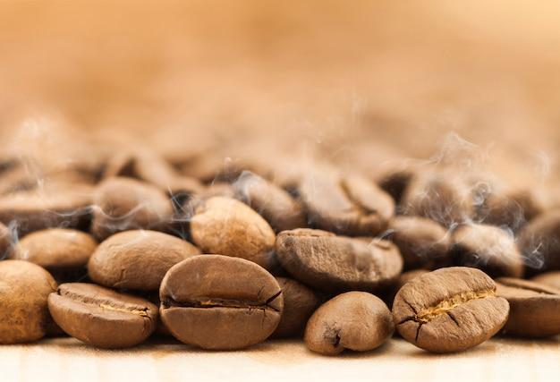 Grains de café brun avec de la vapeur de fumée blanche sur fond de planche de bois texturé jaune se bouchent.