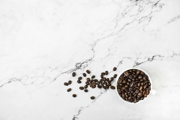 Grains de café bruns avec du café sur un fond de marbre avec espace de copie.