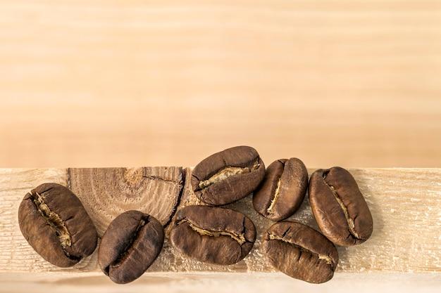 Grains de café bruns sur fond de planche de bois texturé jaune se bouchent.