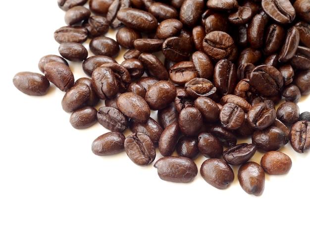 Grains de café bruns isolés sur fond blanc