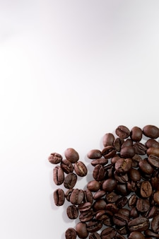Grains de café bruns sur une surface blanche