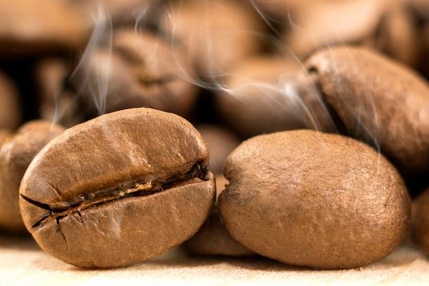 Grains de café bruns avec de la vapeur de fumée blanche sur jaune texturé.