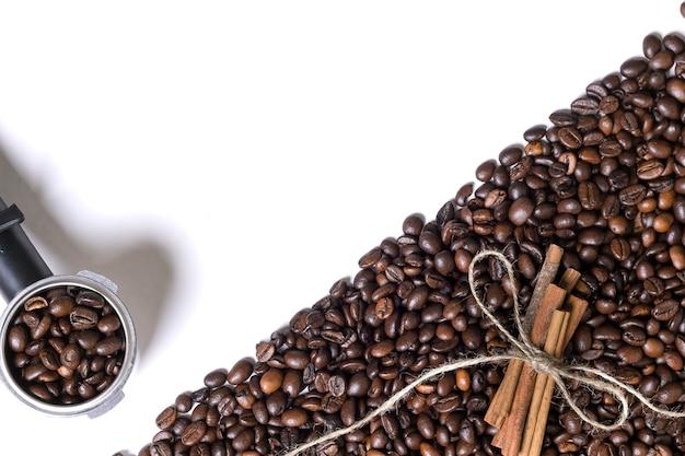 Grains de café et cannelle sur fond blanc. vue de dessus. nature morte. espace de copie. mise à plat.