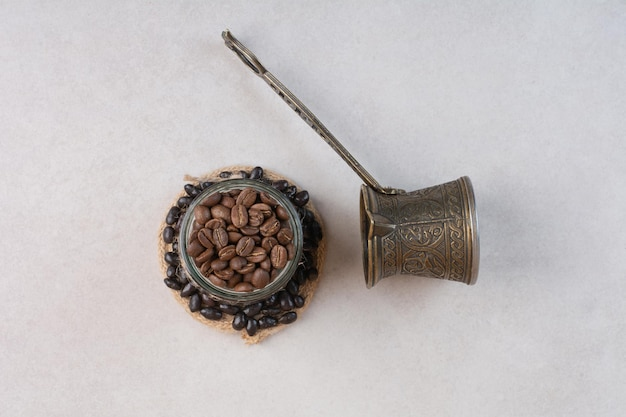 Grains de café et cezve sur fond blanc. photo de haute qualité