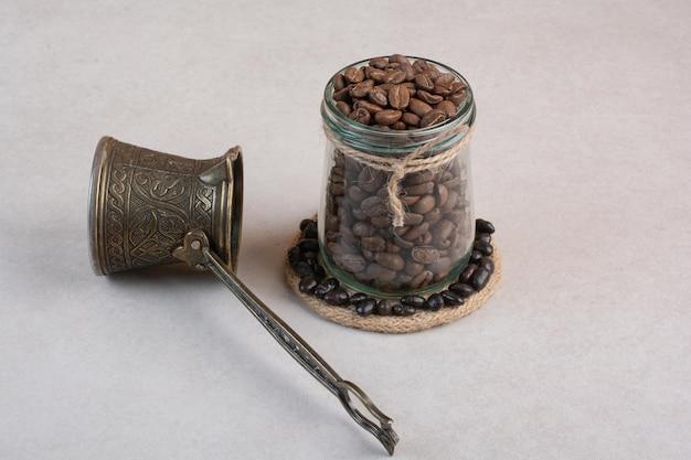 Grains de café et cezve sur surface blanche