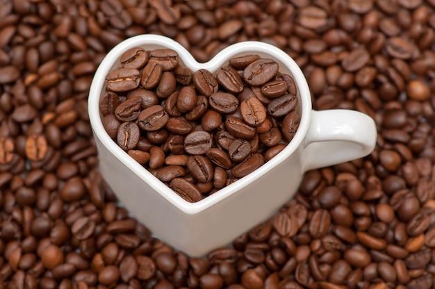 Grains de café coeur de tasse blanche rempli de grains de café sur des grains de café. fermer