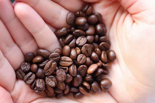 Grains de café couchés dans les mains en forme de coeur gros plan
