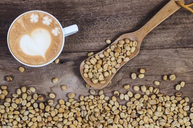 Grains de café cru biologiques avec une tasse de café d'art en retard sur la table en bois.