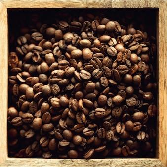 Grains de café crus et torréfiés dans une boîte en bois. ingrédients pour boisson au café. aliments