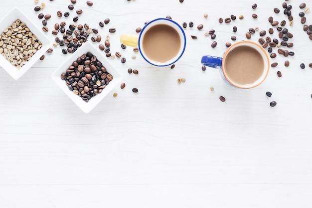 Grains de café crus et torréfiés avec une tasse de café sur un fond en bois blanc