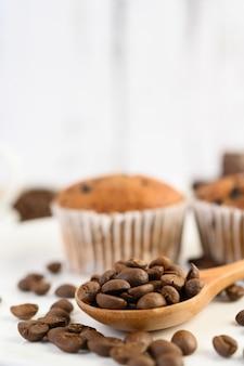 Grains de café sur une cuillère en bois et des cupcakes à la banane sur une table en bois blanc.