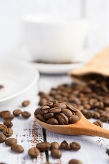 Grains de café sur une cuillère en bois et des sacs de chanvre sur une table en bois blanc.