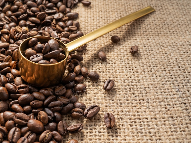 Grains de café avec cuillère à mesurer en or sur fond de texture de lin