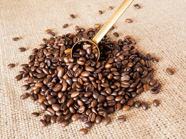Grains de café avec cuillère à mesurer en or et tasse à mesurer sur fond de texture de lin