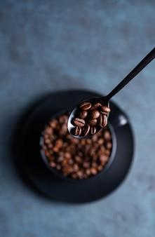 Grains de café en cuillère noire sous tasse sur fond bleu. vue de dessus