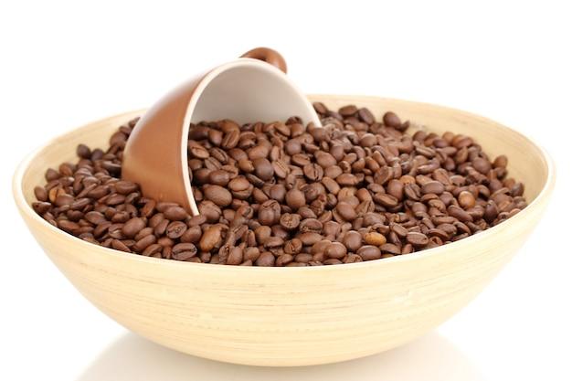 Grains de café dans un bol en bambou avec tasse isolé sur une surface blanche