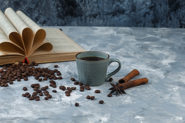 Grains de café dans un bol en bois avec livre, cannelle, tasse de café gros plan sur un fond de marbre bleu clair et foncé